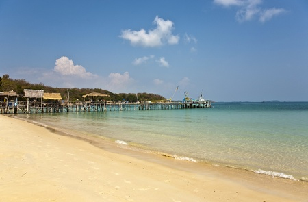 beautiful beach with wooden pier in bay with blue sky photo