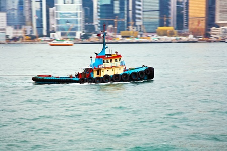 panning shot: Landscape of Victoria Harbor in Hong Kong with famous star ferry on the ocean with tall buildings and skyscrapers