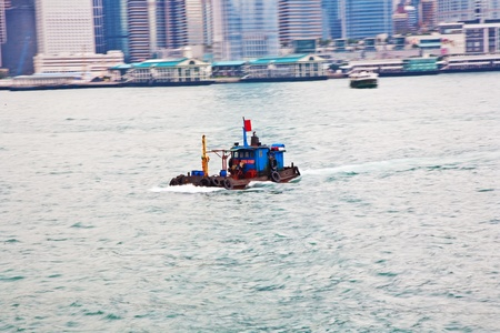 panning shot: Landscape of Victoria Harbor in Hong Kong with ships on the ocean with tall buildings and skyscrapers