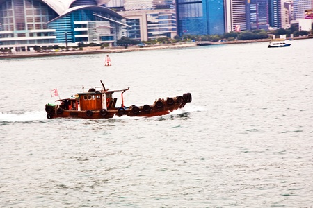 panning shot: Landscape of Victoria Harbor in Hong Kong with junk boat on the ocean