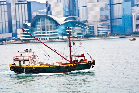 panning shot: Landscape of Victoria Harbor in Hong Kong with motorboad and people on deck