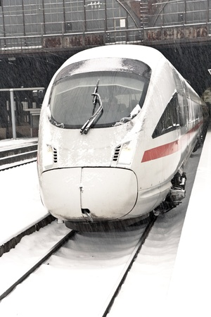 high speed train in station with snow covered rails
