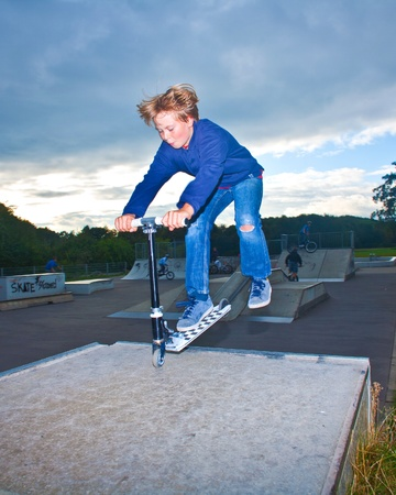 boy jumping with scooter over the ramp at the skate park photo