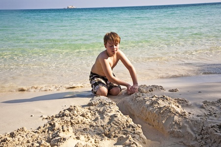 boy plays at the beautiful beach with sand and building figures Stock Photo - 9348864