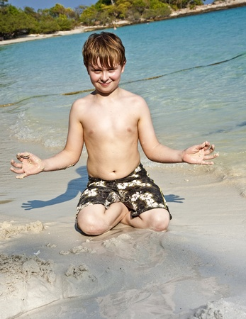boy plays at the beautiful beach with sand and giving signs with his hands photo