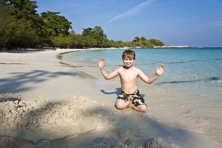 boy plays at the beautiful beach with sand and giving signs with his hands Stock Photo - 9348199