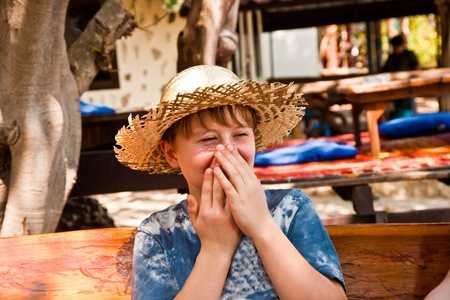 boy is relaxing, smiling and happy and has a rest in the sun at an open air restaurant photo