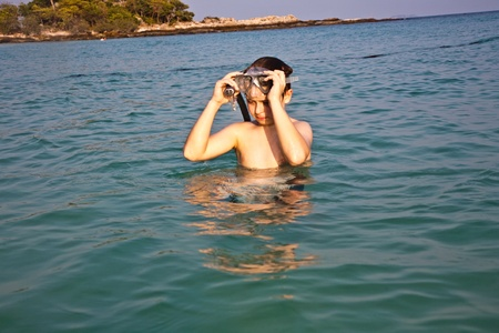young boy is standing in the beautiful clear sea, enjoying the water and starts snorkeling photo