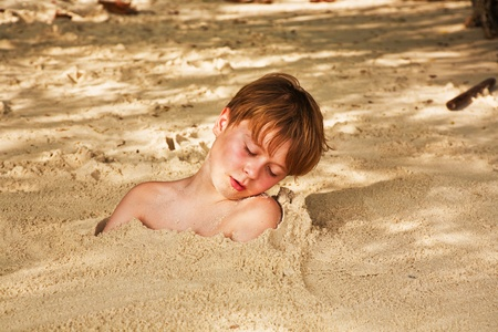 happy young boy covered by fine sand at the beach photo