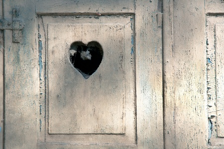 meran: old wooden door in meran, Tirol, Italy with a carved romantic heart Stock Photo