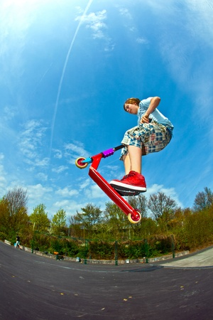 boy is jumping with a scooter over a spine in the skate parc and enjoying it photo