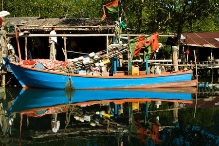huts and colorful  fisherboats at the mangrove everglades in a small fishermans village in Koh Chang photo