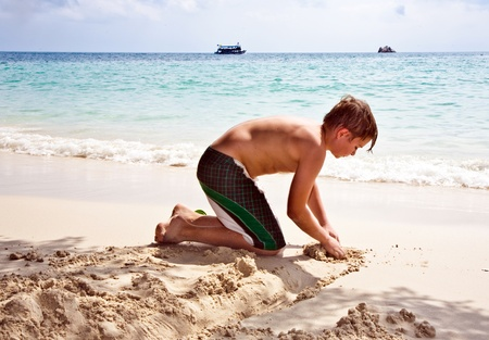 happy boy is building a canal out of sand at the bea Stock Photo - 9375022