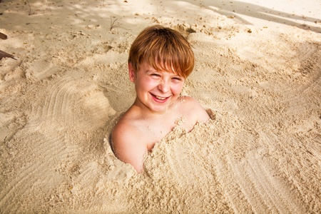 happy young boy covered by fine sand at the beach Stock Photo - 9375114