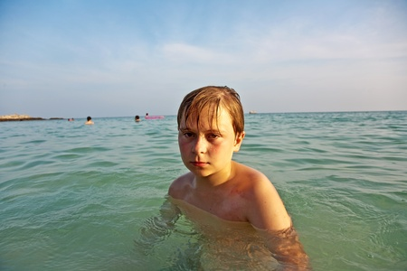 angry young boy is walking thru the clear warm saltwater at the beautiful beach photo