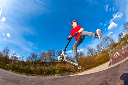 Boy riding a scooter is jumping at a scooter park photo