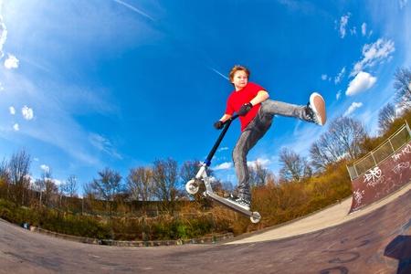 vespa: Ni�o montando un scooter es saltar en un parque de scooter