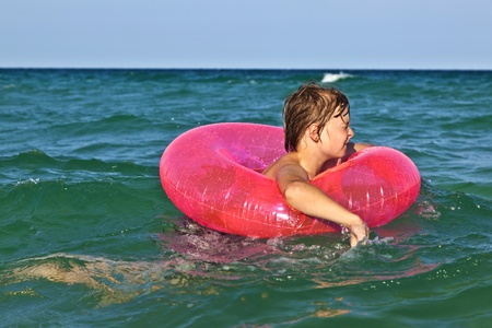 happy boy in a swim ring has fun in the ocean Stock Photo - 9375117