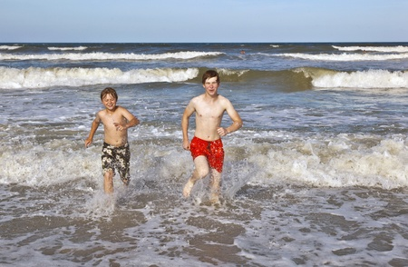 boys having fun in the beautiful clear sea photo