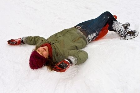 girl lying in the snow from sledging down the hill in winter Stock Photo - 9398409