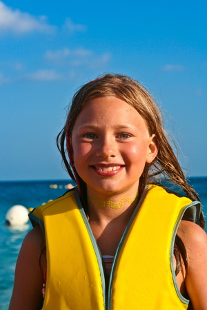 lifevest: cute young girl at the beach with wet hair Stock Photo