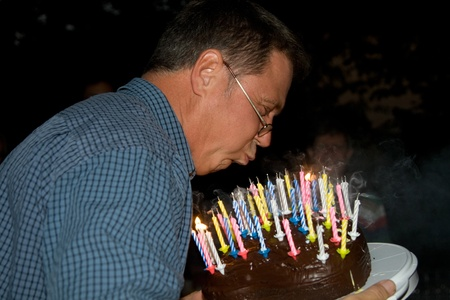 man blows out his birthday candles at the birthday photo