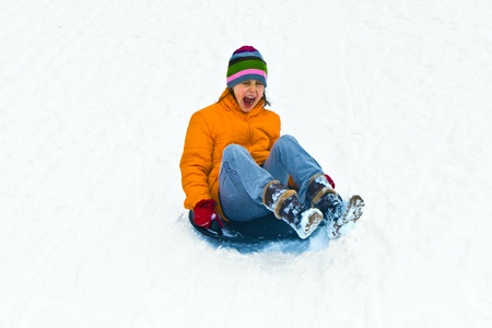 sledging people: girl sliding down the hill in winter