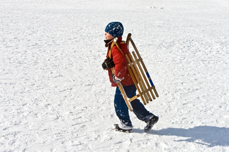 kid friendly: boy is carrying his sledge
