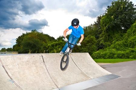boy has fun with his BMX at the skatepark photo