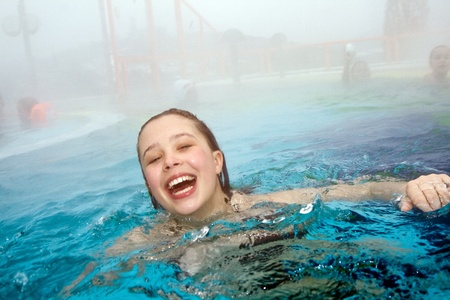 girl has fun in the outdoor thermal pool in wintertime photo