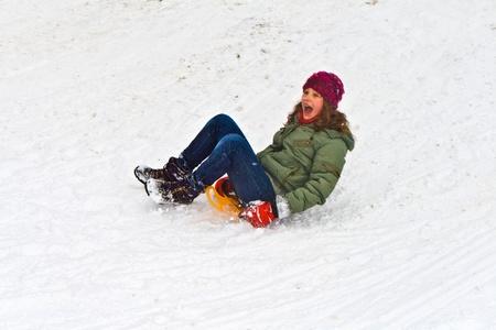 sledging: bella ragazza slittino gi? per la collina sulla neve Archivio Fotografico