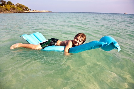 brotherly love: boy lying face forward on air mattress on sea