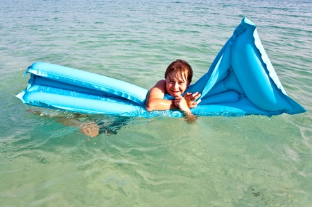 brotherly love: boy with red hair is enjoying the air mattress on crystal clear water