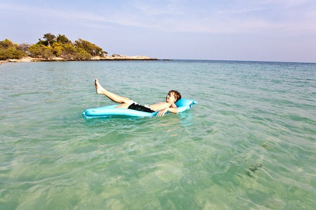 boy enjoying the sea on an air mattress photo