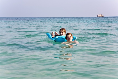 brotherly love: two boys are playing together in beautiful sea with crystal clear water and blue sky