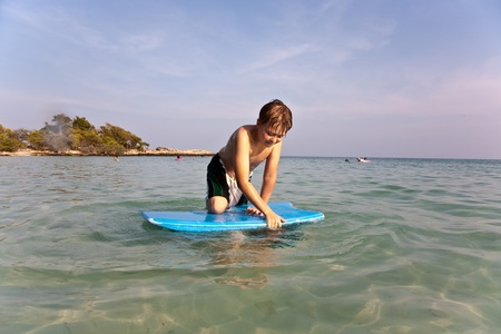 boy is surfing on a small surfboard in a beautiful sea with crystal clear water and blue sky photo