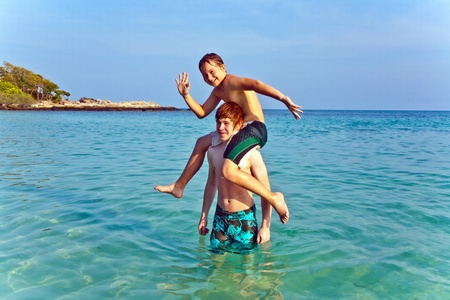 brotherly love: brothers are playing together in a beautiful sea with crystal clear water and blue sky