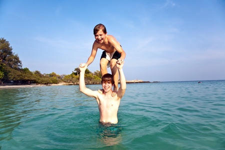 brothers are playing together jumping from shoulder in the sea  in crystal clear water with blue sky photo