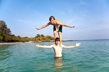 brothers are playing together jumping from shoulder in the sea  in crystal clear water with blue sky Stock Photo