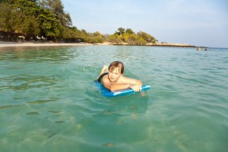 boy is swimming on his surfboard and happily smiling in  a beautiful sea with crystal clear water and blue sky Stock Photo - 9444221