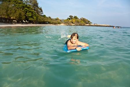 boy is swimming on his surfboard and happily smiling in  a beautiful sea with crystal clear water and blue sky Stock Photo - 9444079