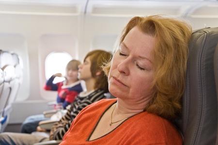 cansancio: Mujer durmiendo en el avi�n Foto de archivo