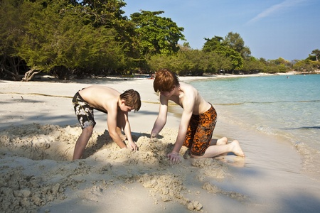 dug: boys are playing at the beautiful beach with sand and building figures Stock Photo