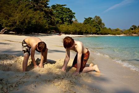 giovani ragazzi stanno godendo giocare in spiaggia e la costruzione di figure out di sabbia presso la bellissima spiaggia bianca