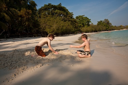 young boys are enjoying playing at the beach and building figures out of sand at the beautiful white beach photo