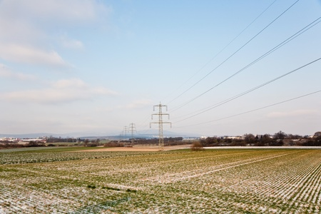 acres with snow in winter with electricity tower in beautiful light and structure photo