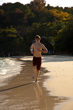 boy with red hair in bathing cloths is walking on a beautiful beach and enjoing it Stock Photo - 9583284