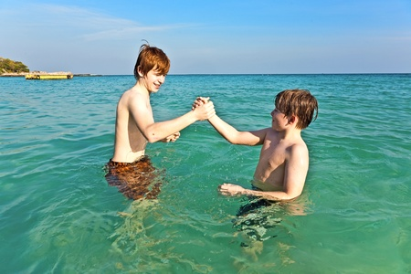 brothers are enjoying the clear warm water at the beautiful beach Stock Photo - 9583346