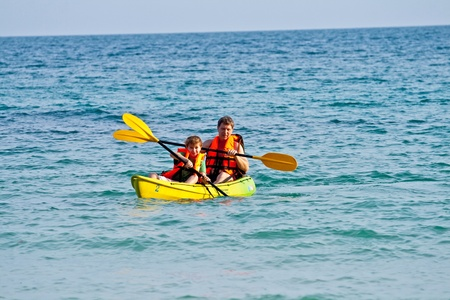 boat party: father and son are padelling with a canoe on open sea