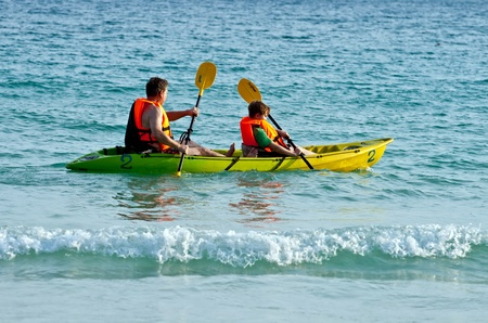 father and son are padelling with a canoe on open sea Stock Photo - 9583320